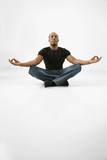 young male adult sitting meditating. poster