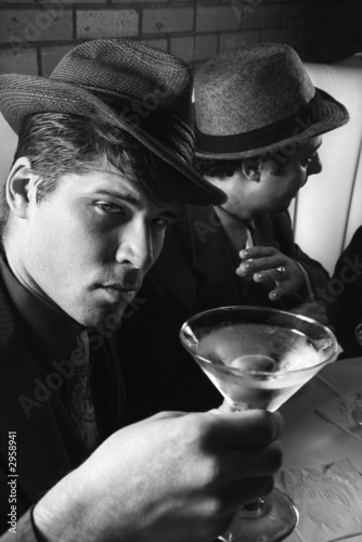 two retro businessmen sitting at table with cocktails.