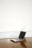laptop on hardwood floor. poster