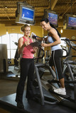 adult female on elliptical machine with trainer. poster