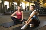 adult female with personal trainer at gym. poster