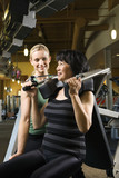 adult female trainer helping adult female on exercise machine. poster