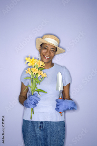 woman with hand shovel and flowers.