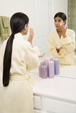 Young woman looking in mirror applying facial scrub. poster