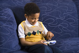 Young boy playing video game on couch. poster