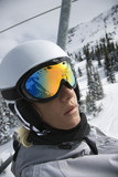 Teenage boy riding chair lift at ski resort. poster