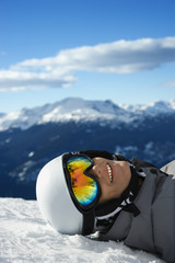 Boy snowboarder lying on mountain.