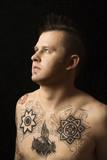 Shirtless Caucasian man with tattoos. poster