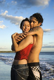 Young adult couple embracing on beach. poster