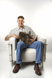 Caucasian man sitting holding Persian cat. poster