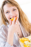a blond woman biting a slice of orange poster