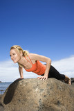 Woman doing push up on rock. poster