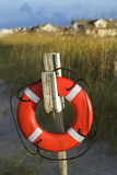 Life preserver hanging on post on beach. poster