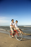 Dad riding red bicycle with son on handlebars. poster