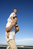 Dad carrying son on his shoulders. poster