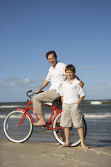 Father on bike with arm around son on beach.