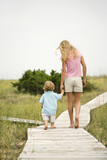 Girl walking on beach walkway with little boy. poster