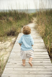 Little boy walking down beach walkway. poster
