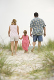 Mom, Dad and daughter walking toward beach. poster