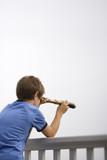 Boy looking through telescope. poster