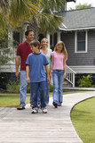 Family of four walking down sidewalk. poster
