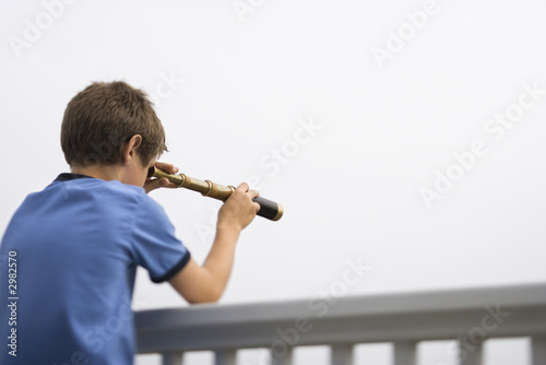 Boy looking through telescope.