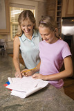 Mom helping daughter with homework at kitchen counter. poster