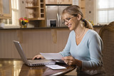 Woman paying bills on computer. poster