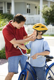 Dad helping son with bicycle helmet. poster