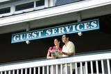 Couple looking out at guest services. poster