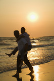 Man carrying woman on beach at sunset. poster