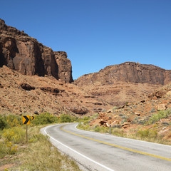Road curving to right with red rock cliffs in Utah.