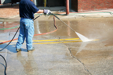 a crew member cleans the painted street markings