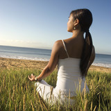 woman sitting on beach and meditating. poster