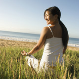 woman sitting on beach meditating. poster