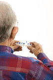 elderly man holding seven-day pill box. poster