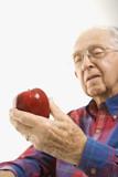 elderly man holding apple. poster