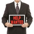 businessman holding help wanted sign.