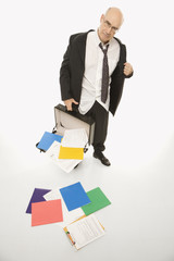 businessman losing papers from briefcase.