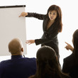 businesswoman giving presentation in front of others.