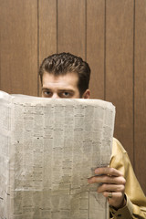 retro businessman peeking over newspaper.