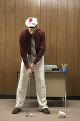 retro businessman playing golf in office.
