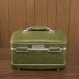 still life shot of a vintage green luggage piece sitting on a wo poster