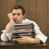 man with overwhelmed face holding lots of paperwork poster