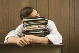 man resting head on stack of paperwork. poster