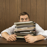 man peeking over big stack of paperwork. poster