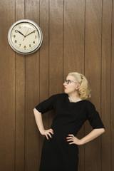 woman looking up at clock on wall.