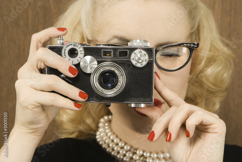woman holding a vintage camera up to her face.