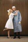 female nurse kissing surgeon on cheek. poster