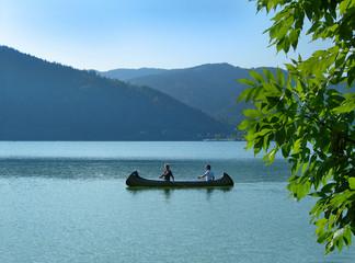 women paddling canoe on lake